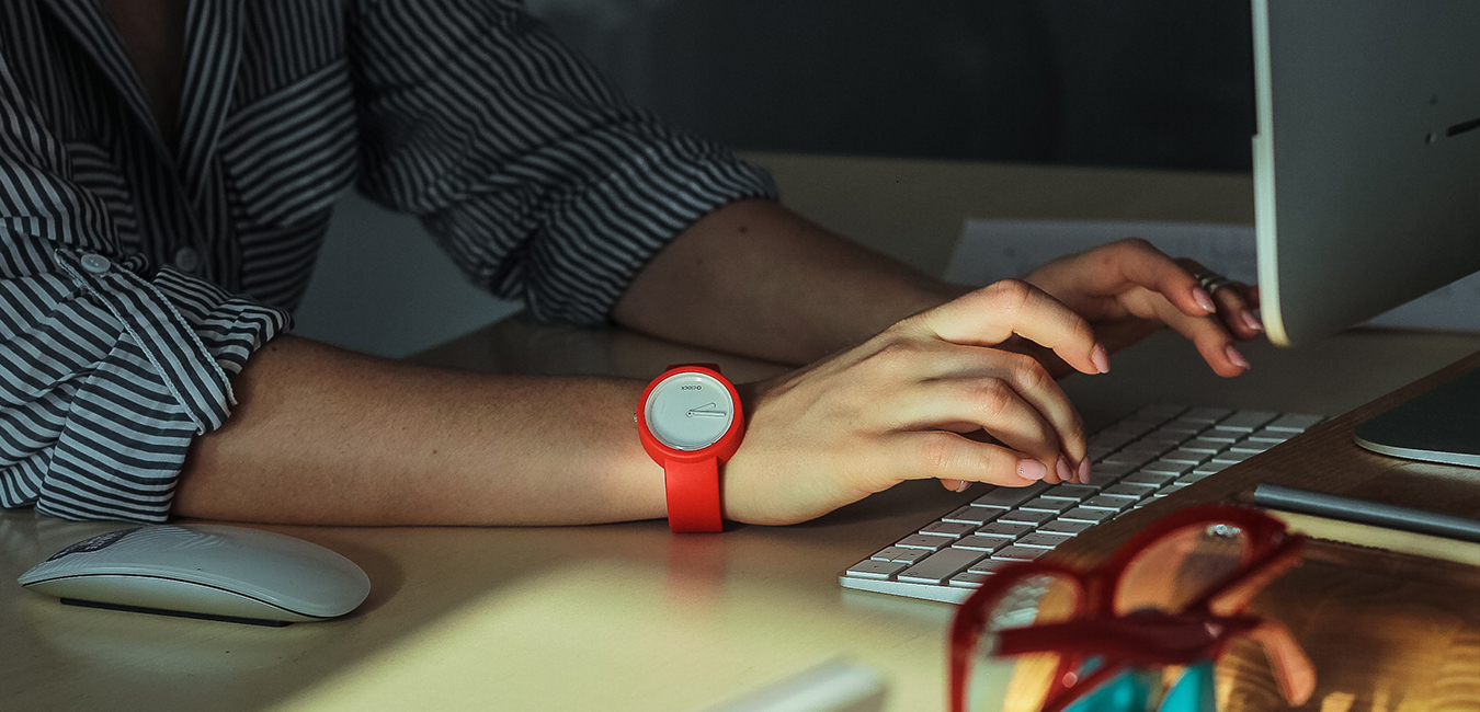 Woman wearing a red watch typing on a computer