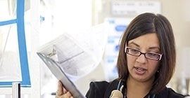 Woman looking through papers on a clipboard